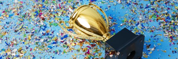 Gold trophy on a confetti background